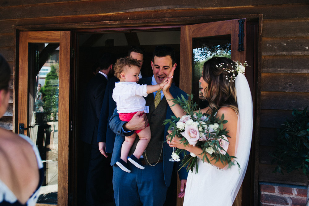 a bride high-five's a toddler guest at her wedding