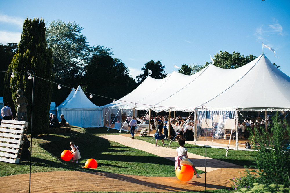 wide shot of a white marquee with kids on orange space hoppers in the foreground