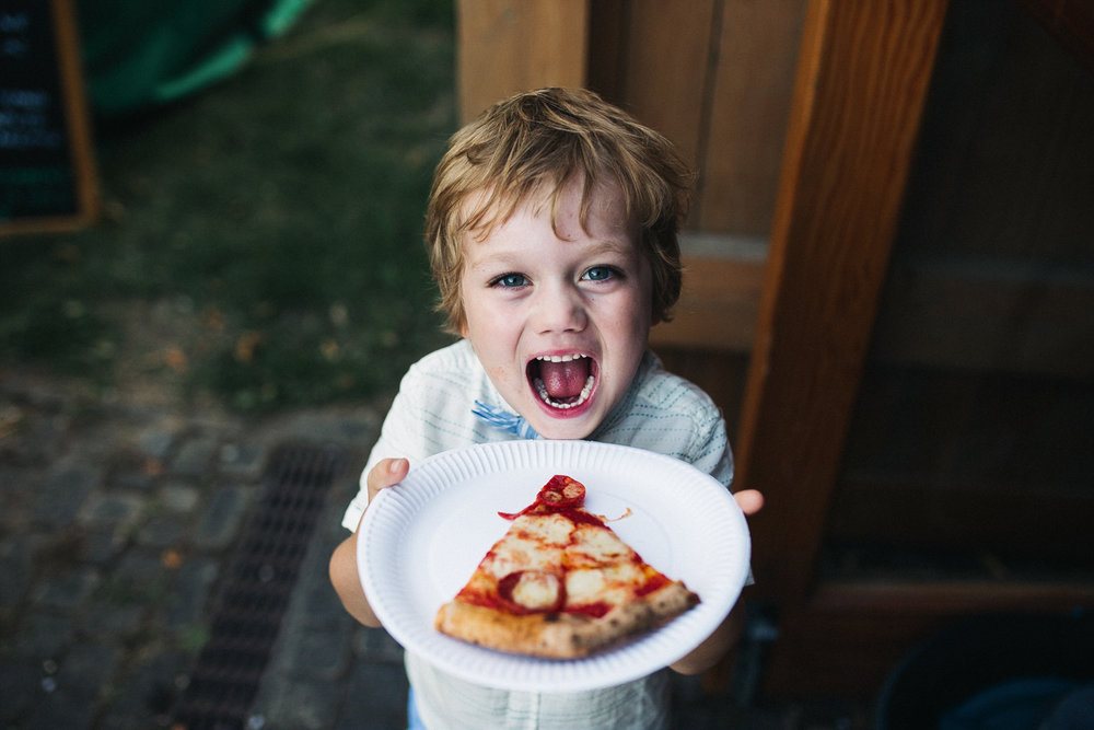 a boy holds pizza and looked overjoyed
