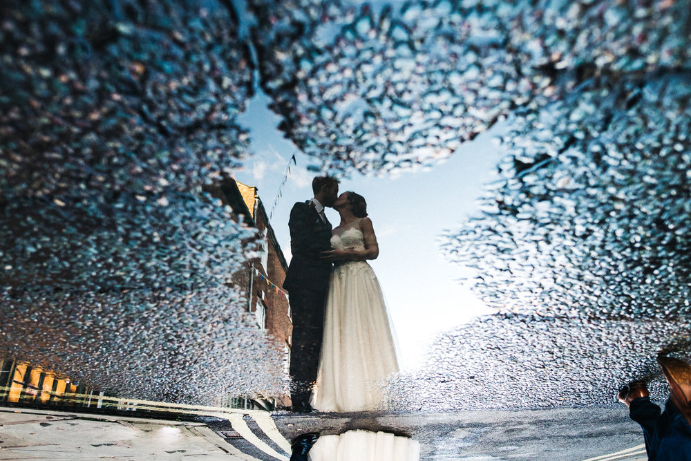 a bride and groom's reflection in a puddle, they are kissing