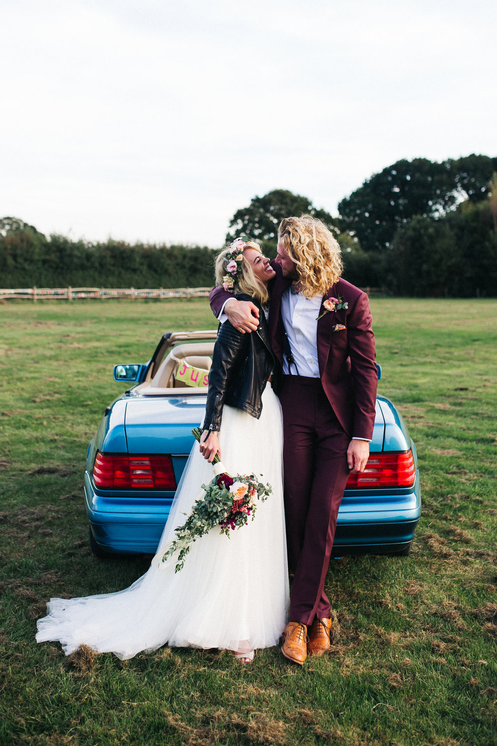 a bride and groom stand in front of a 90s blue car. she's wearing a white dress and a black leather jacket and he's wearing a burgundy suit