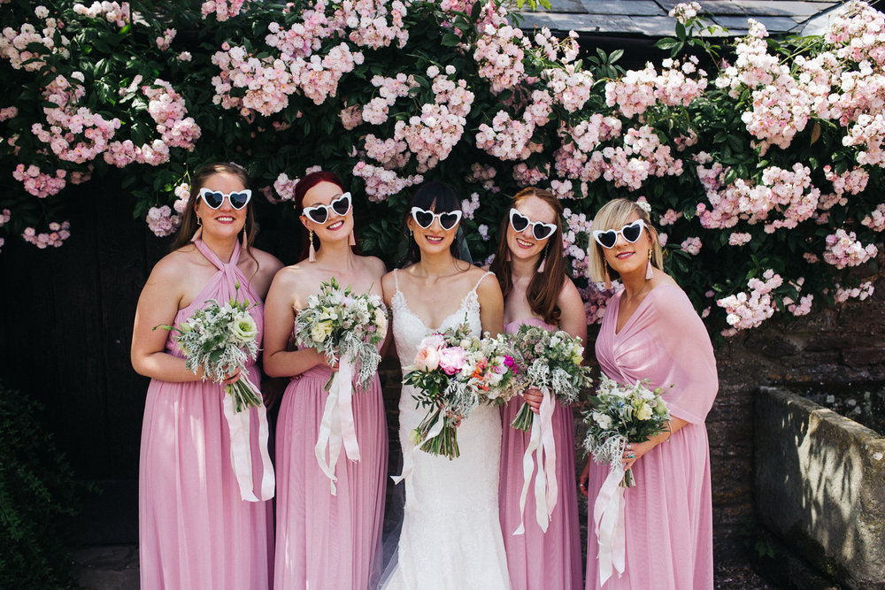 bridesmaids and a bride, in pink, standing in white sunglasses in front of pink flowers