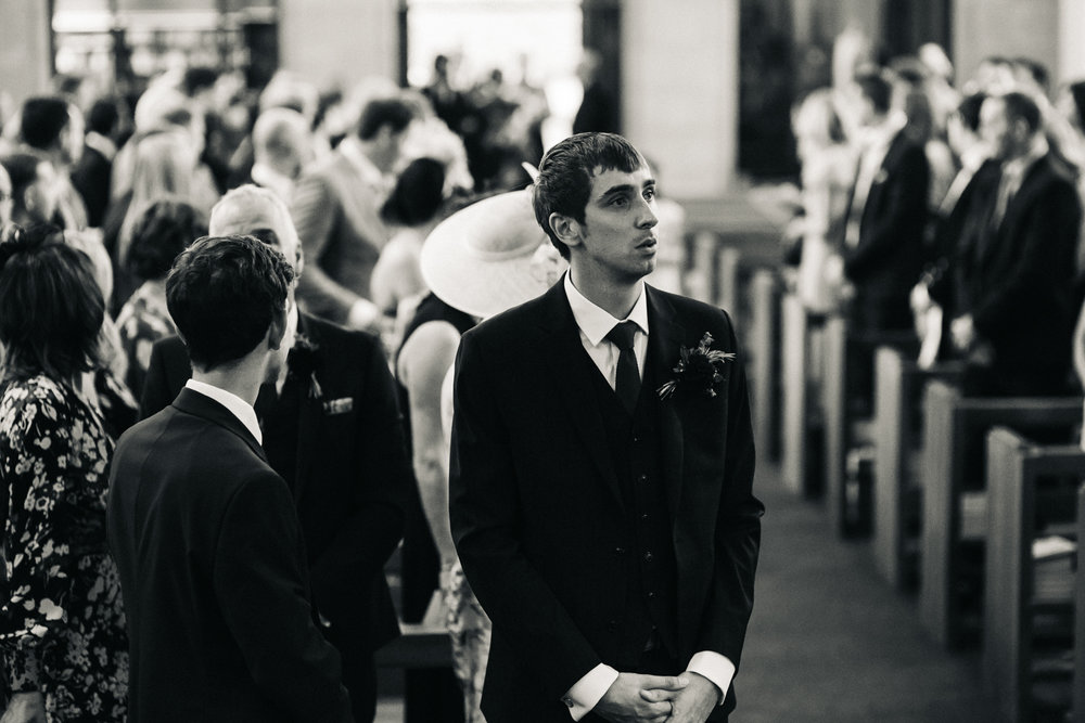 a groom looks overwhelmed as his future wife walks down the aisle