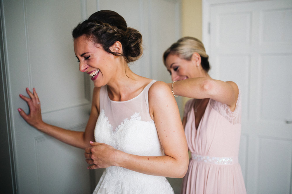 a bride laughs as her bridesmaid does her dress up