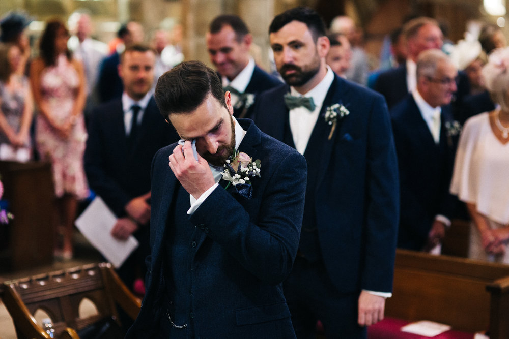 a groom holds a tissue to his eye in church