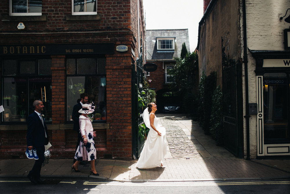 a bride walks down the street and looks happily up at the sky when she steps into the sunshine