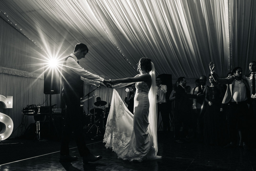 a black and white photo of a bride and groom dance in front of their guests