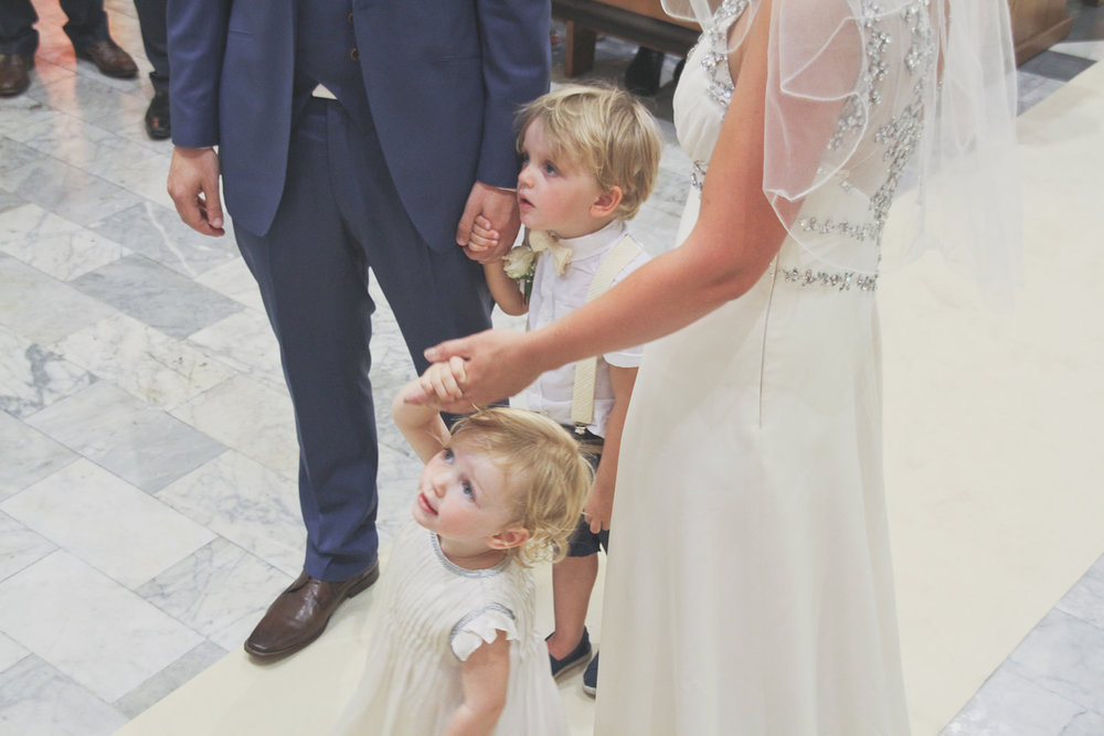 a boy and girl stand with their parents as they get married. destination wedding photography in italy, rome. stop motion wedding films