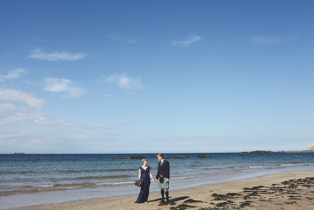 a man and woman stand on the beach. wide shot. scotland outdoor humanist beach wedding. stop motion wedding films uk
