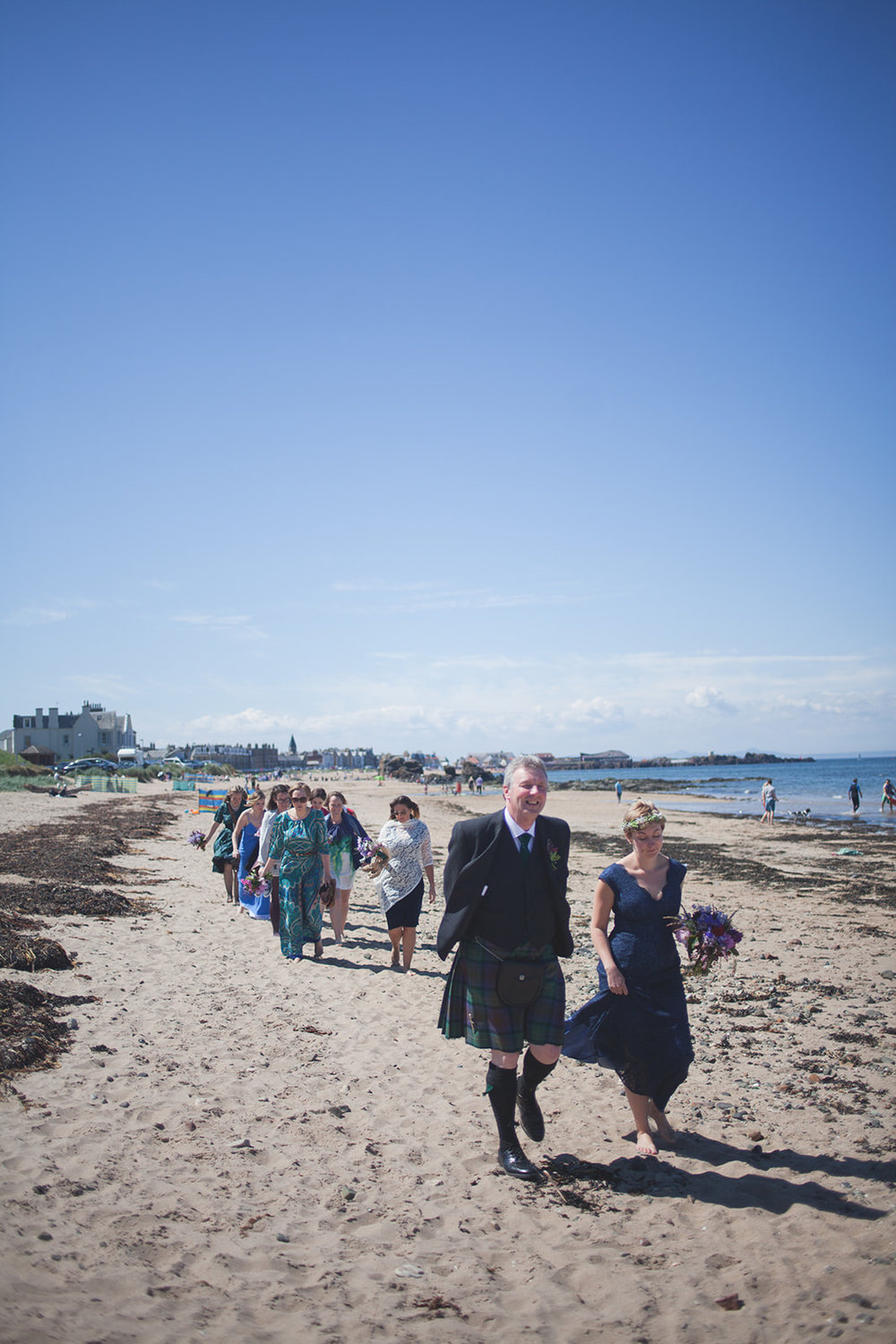 a bridal party walk down the beach towards the ceremony. scotland outdoor humanist beach wedding. stop motion wedding films uk