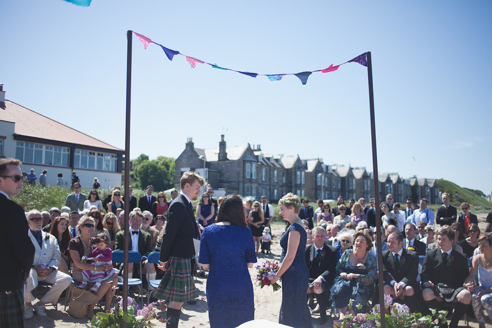 a bride and groom stand under an alter with bunting. scotland outdoor humanist beach wedding. stop motion wedding films uk