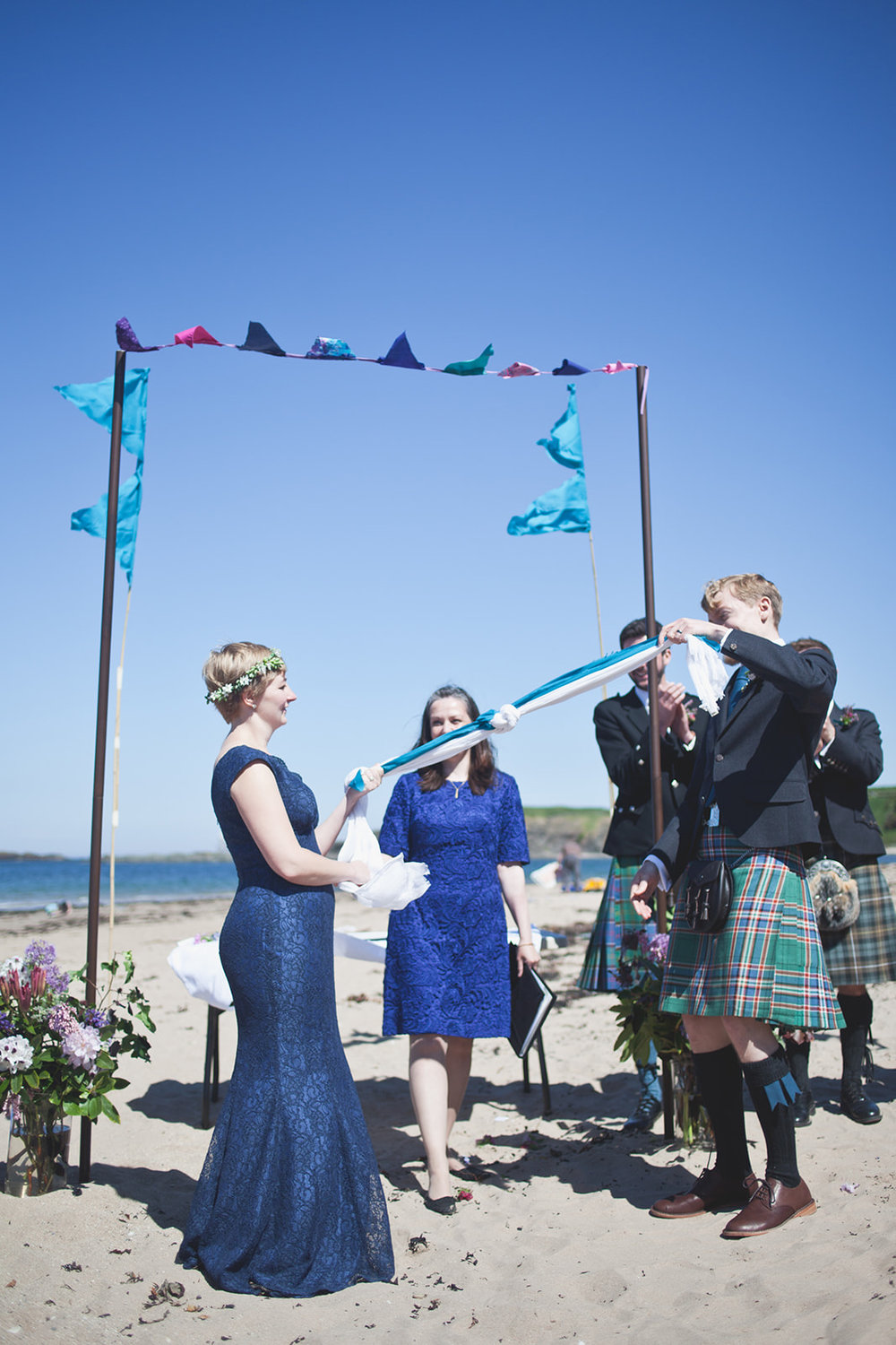 a bride and groom pull the hand fasting scarf during their ceremony. scotland outdoor humanist beach wedding. stop motion wedding films uk