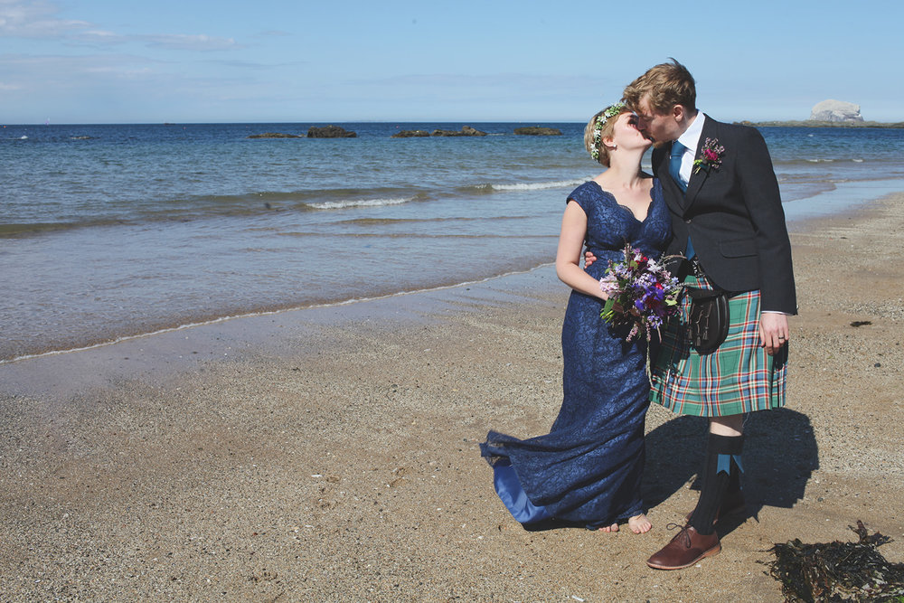 a bride and groom kiss on the beach. scotland outdoor humanist beach wedding. stop motion wedding films uk