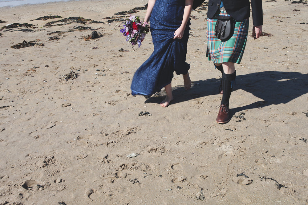 a cropped shot of the bride and groom's feet walking along the sand. scotland outdoor humanist beach wedding. stop motion wedding films uk