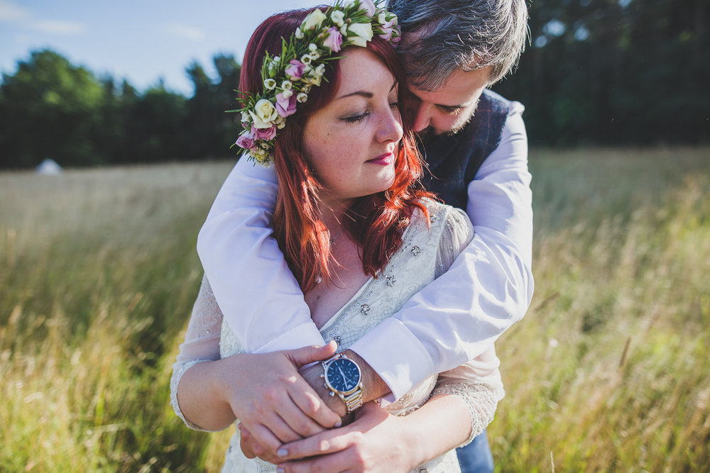 a bride and groom hug closely in a field. camp katur wedding north yorkshire tipi wedding venue glamping. stop motion wedding films uk