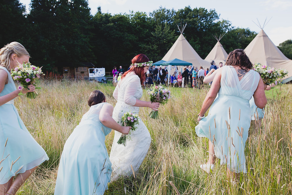 a bride and her bridesmaids walk through the field towards a tipi. camp katur wedding north yorkshire tipi wedding venue glamping. stop motion wedding films uk