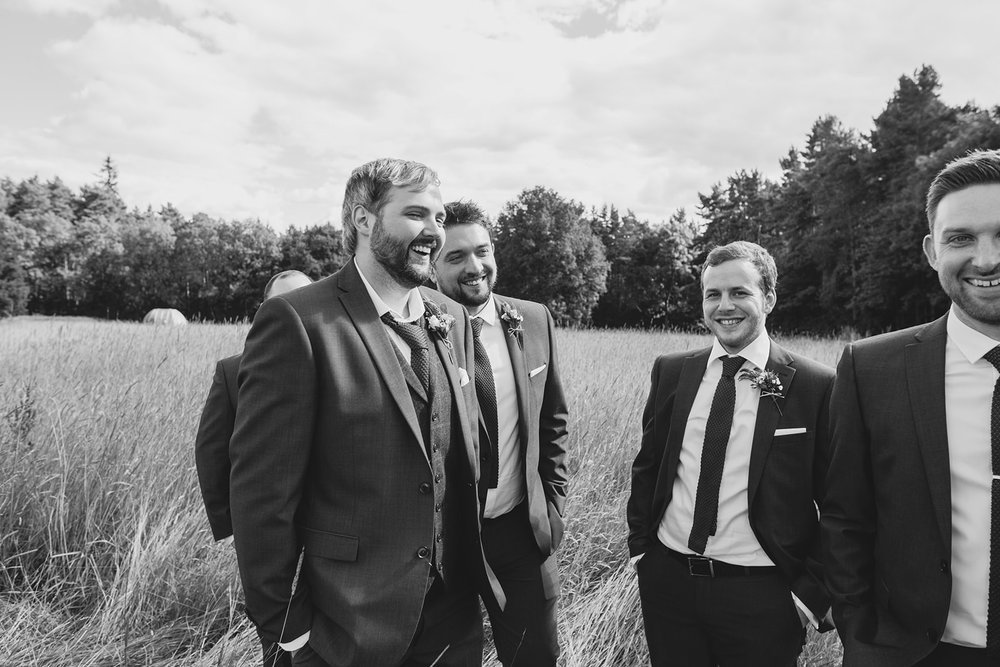 a groom and the groomsmen stand laughing together in a field. camp katur wedding north yorkshire tipi wedding venue glamping. stop motion wedding films uk