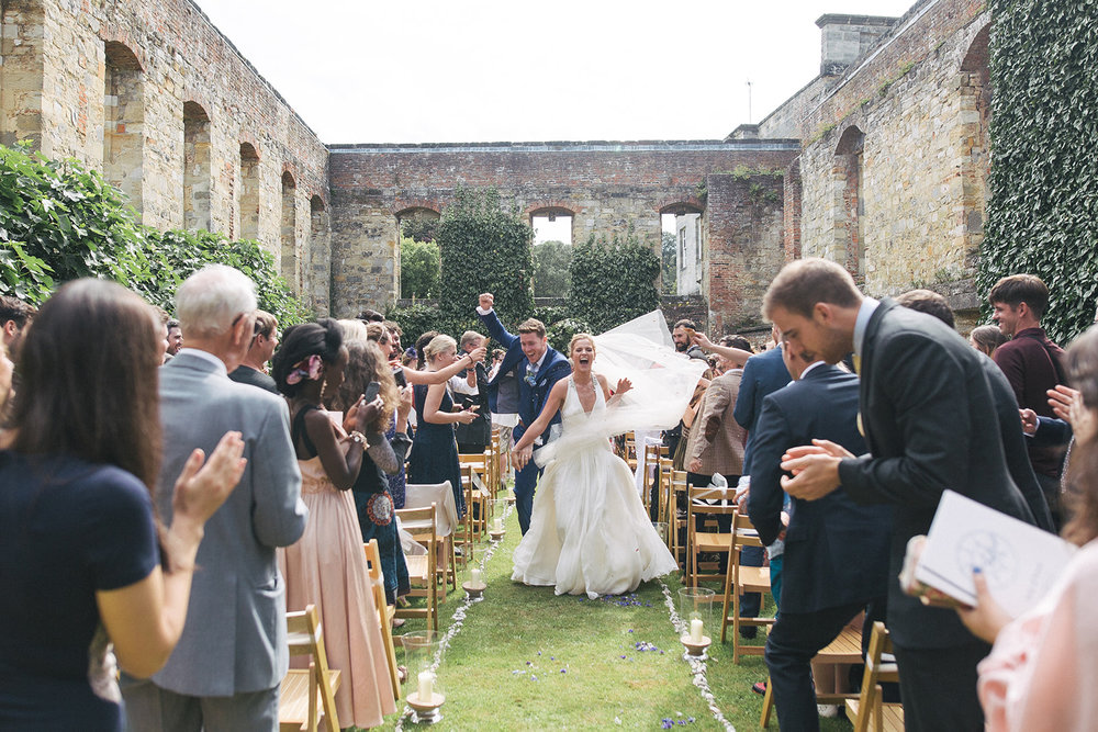 a bride and groom look joyous as they walk back down the aisle. newburgh priory north yorkshire outdoor marquee wedding. stop motion wedding films uk