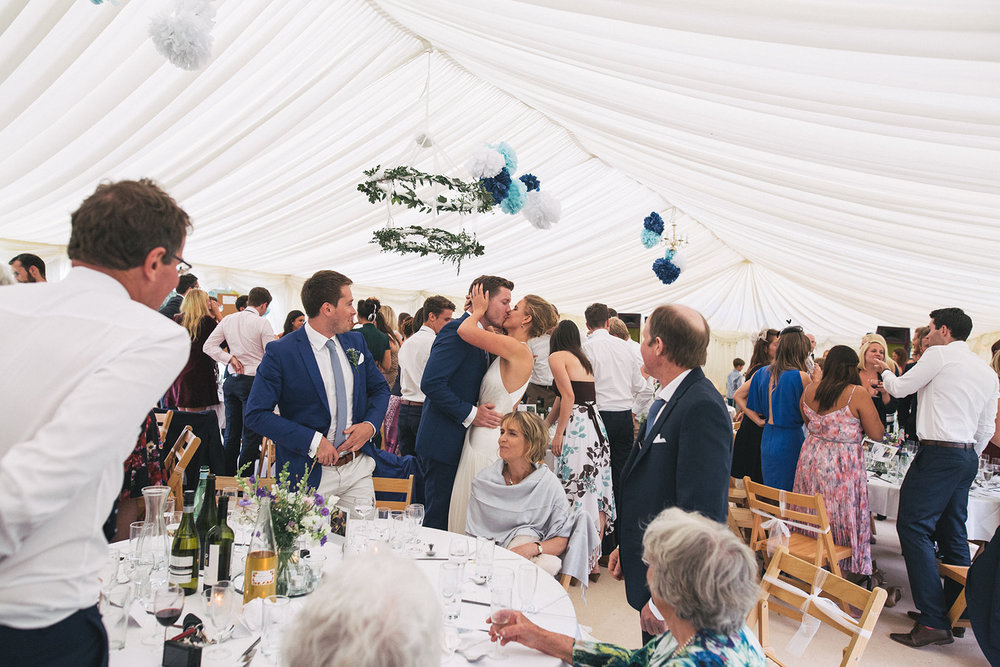 a bride and groom kiss amongst the chaos of a marquee full of guests. newburgh priory north yorkshire outdoor marquee wedding. stop motion wedding films uk