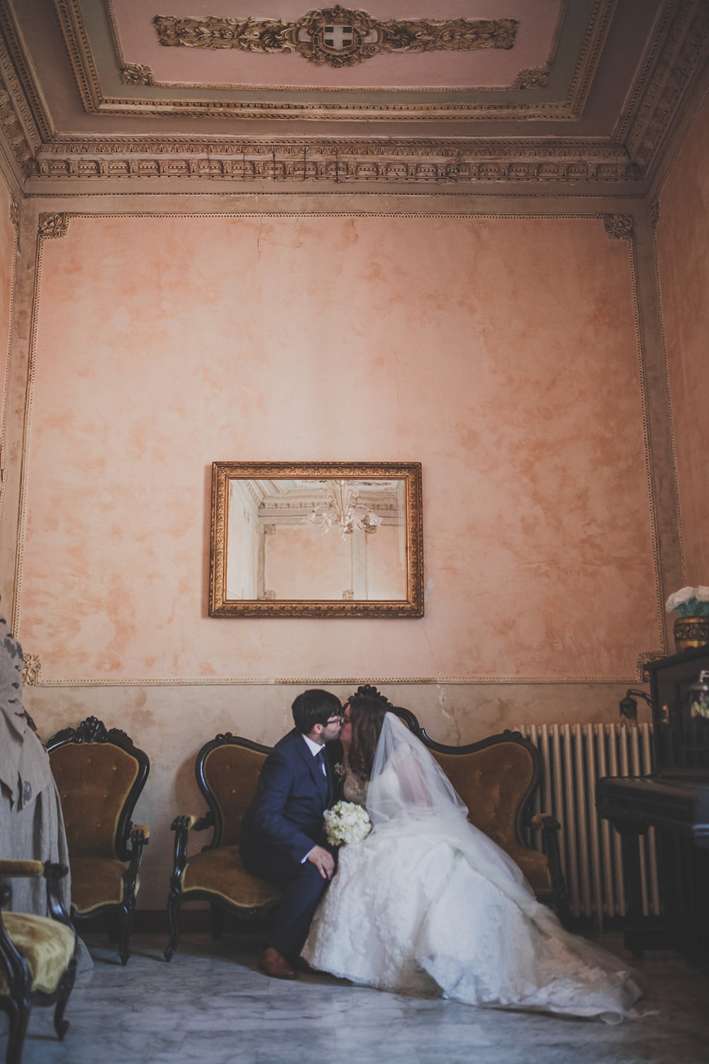 a bride and groom sit on a sofa and kiss in a grand room. destination creative wedding photography italy. stop motion wedding films uk