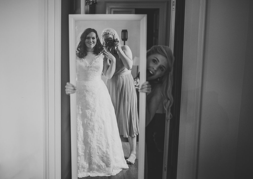 a bride and her bridesmaids look into the mirror at her reflection. destination creative wedding photography italy. stop motion wedding films uk