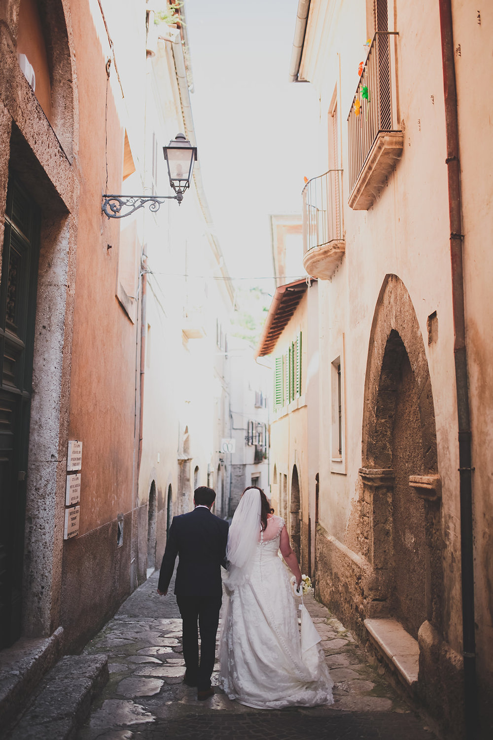 a bride and groom walk down a tall italian street. destination creative wedding photography italy. stop motion wedding films uk
