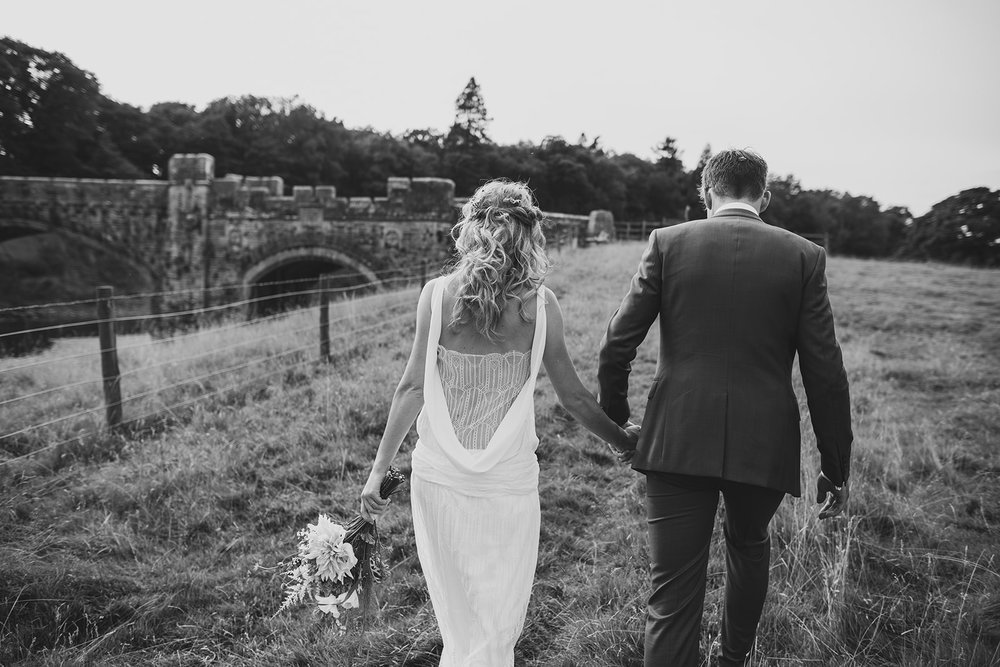 a black and white shot of a bride and groom walking away from the camera. underlay grange marquee wedding lake district. stop motion wedding films uk