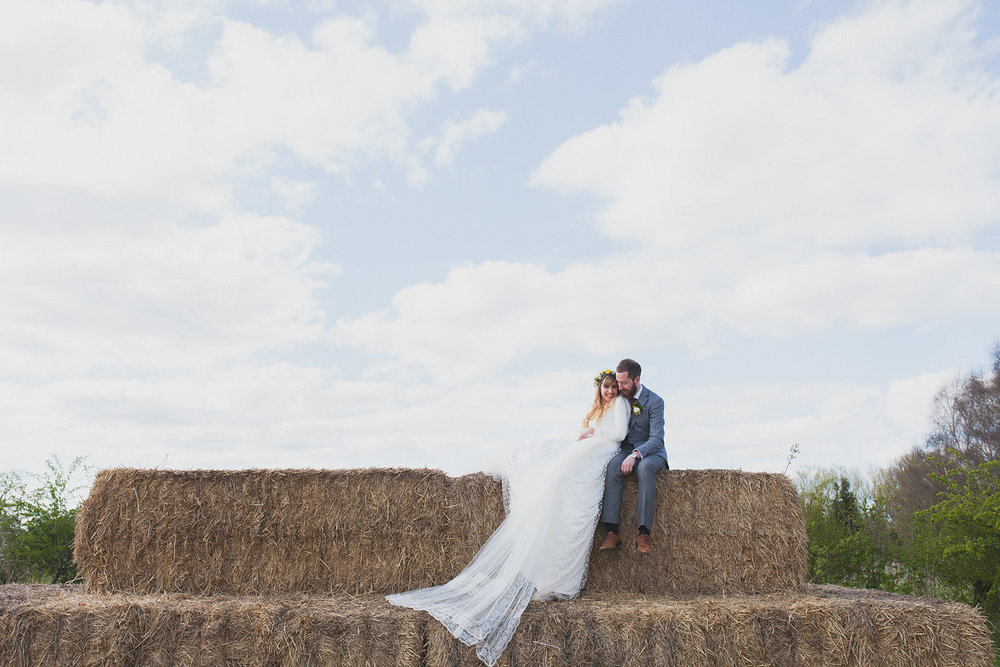a bride and groom sit on a haystack. york maze barn wedding, york city, north yorkshire wedding photographer. stop motion wedding films UK.