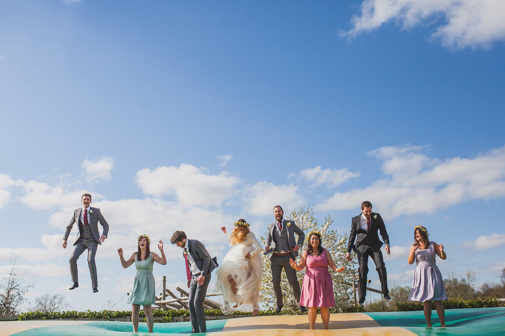 the bride, groom and bridal party bounce on a huge trampoline. york maze barn wedding, york city, north yorkshire wedding photographer. stop motion wedding films UK.