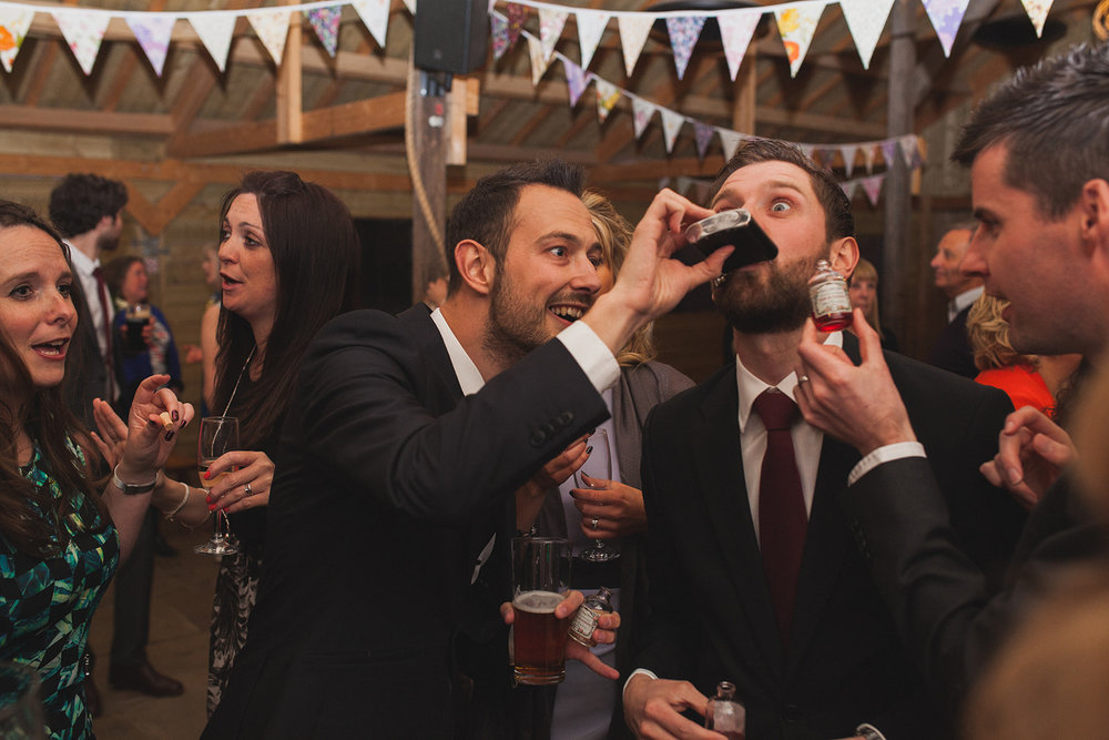a man pours spirit into another man's mouth from a hipflask. york maze barn wedding, york city, north yorkshire wedding photographer. stop motion wedding films UK.
