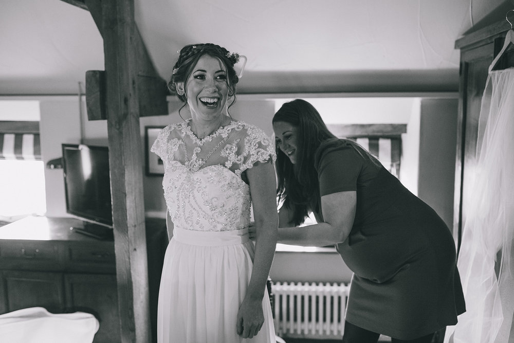 a bride smiles as someone does her dress up. star inn at harome near helmsley, north yorkshire wedding photographer. stop motion wedding films uk.