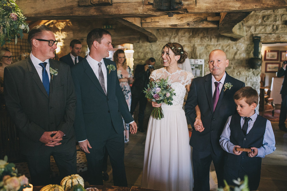 a bride and groom smile at each other at the bottom of the aisle during the ceremony. star inn at harome near helmsley, north yorkshire wedding photographer. stop motion wedding films uk.