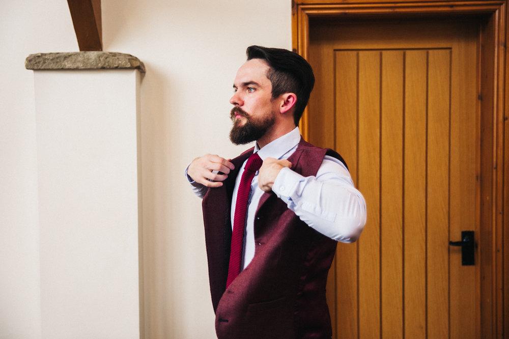 a groom puts his burgundy waistcoat on. intimate winter wedding north east wedding photographer, stop motion wedding films uk