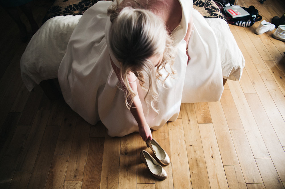 a bride reaches down for her gold wedding shoe. intimate winter wedding north east wedding photographer, stop motion wedding films uk