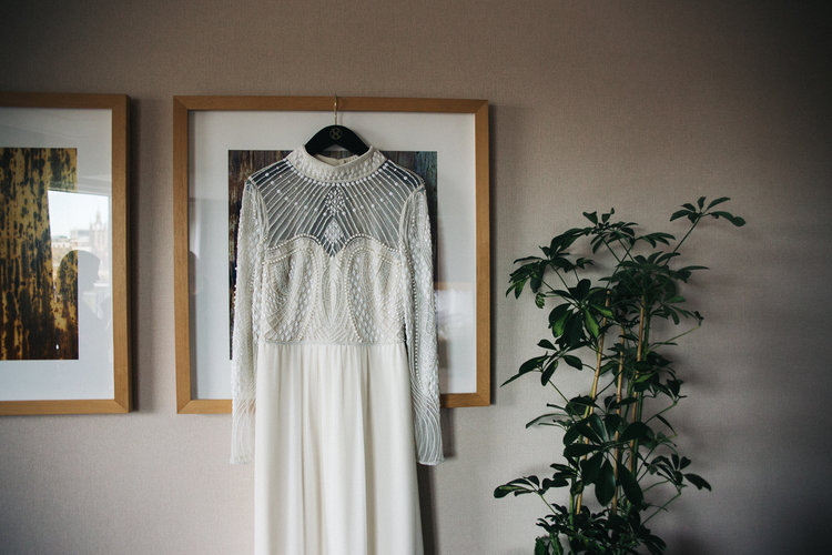 a dress hangs on a photo frame next to a plant. st marys heritage centre wedding gateshead newcastle. wedding photography north east stop motion films uk