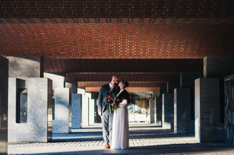 a bride and groom stand in a brutalist architecture corridor. st marys heritage centre wedding gateshead newcastle. wedding photography north east stop motion films uk