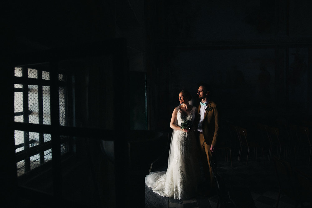 a man and woman stand in the darkness illuminated only by the light through the door. destination wedding at hotel monte rosa in chiavari, italy. stop motion wedding films uk
