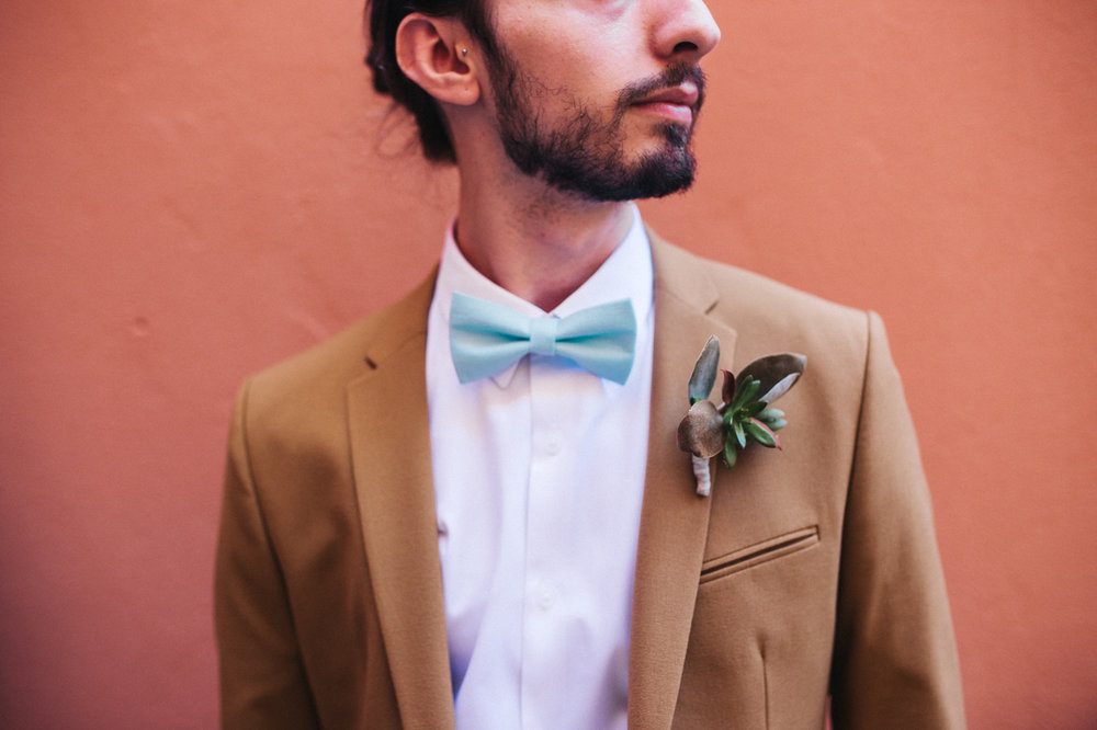 a cropped shot of a groom, he is wearing a turquoise bow tie and succulent corsage. destination wedding hotel monte rosa chiavari italy. stop motion wedding films uk