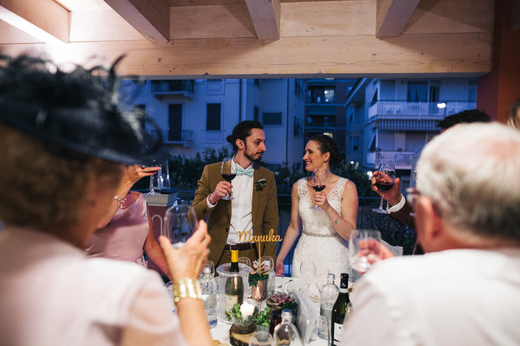 a bride and groom look to each other with glasses of wine in hand during the speeches. destination wedding hotel monte rosa chiavari italy. stop motion wedding films uk