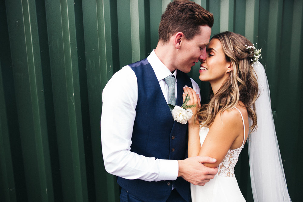 a bride and groom stand against a green iron barn. sandhole oak barn wedding congleton cheshire. stop motion wedding films uk