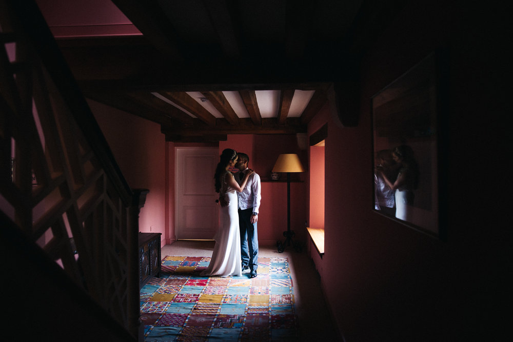 a bride and groom stand, lit by the window. the old hall at ely wedding, cambridge. stop motion wedding films uk