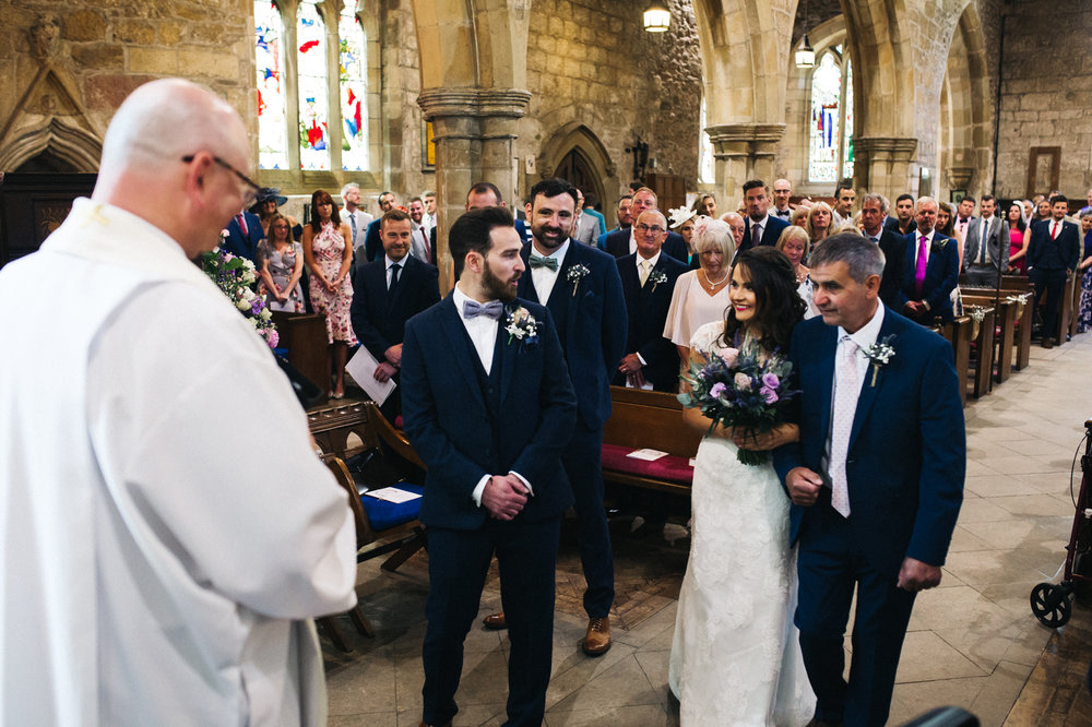 a groom looks happily at his bride at the bottom of the aisle. diy village hall wedding venues north yorkshire northallerton. stop motion wedding films uk