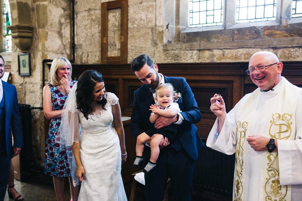 a bride and groom getting their son christened. diy village hall wedding venues north yorkshire northallerton. stop motion wedding films uk