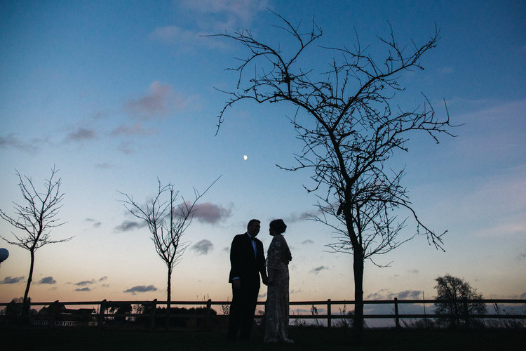 a bride and groom stand against a sunset blue sky. white hart inn derby wedding photographer and stop motion wedding films teesside uk