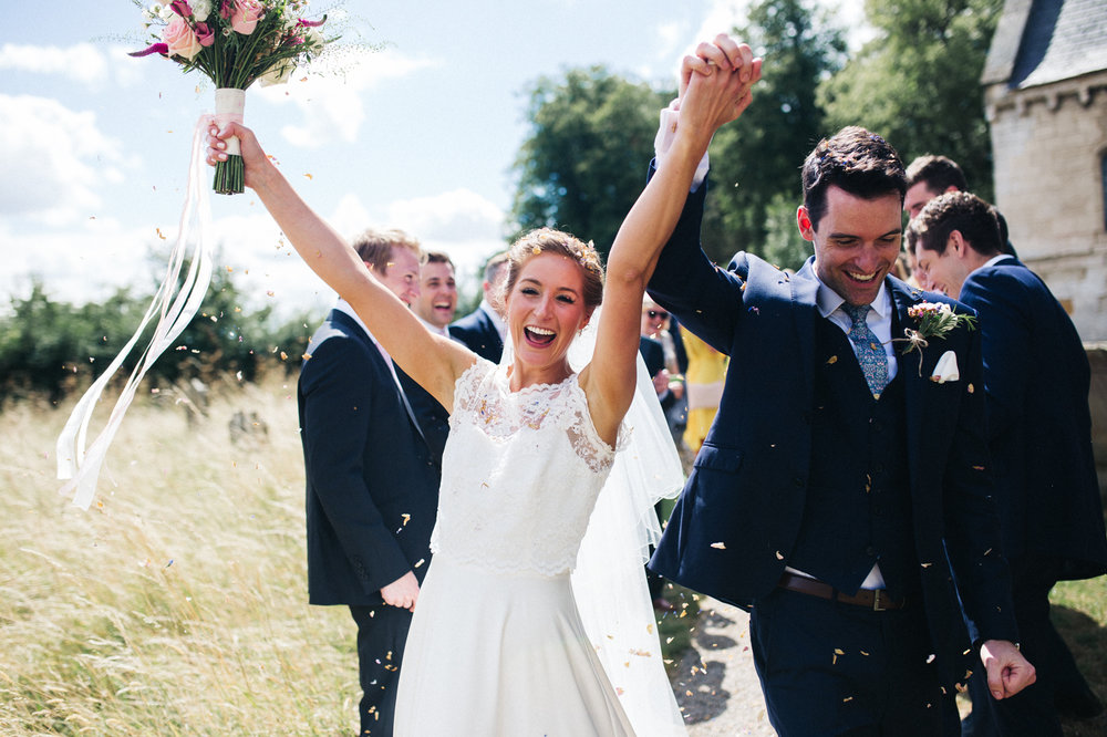a bride and groom cheer outside of church. aldby park wedding york north yorkshire teesside photography stop motion wedding films uk