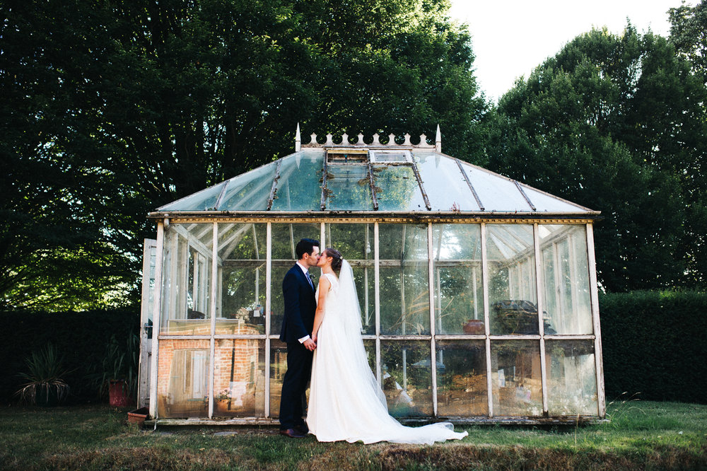 a bride and groom kiss standing outside an old greenhouse. aldby park wedding york north yorkshire teesside photography stop motion wedding films uk