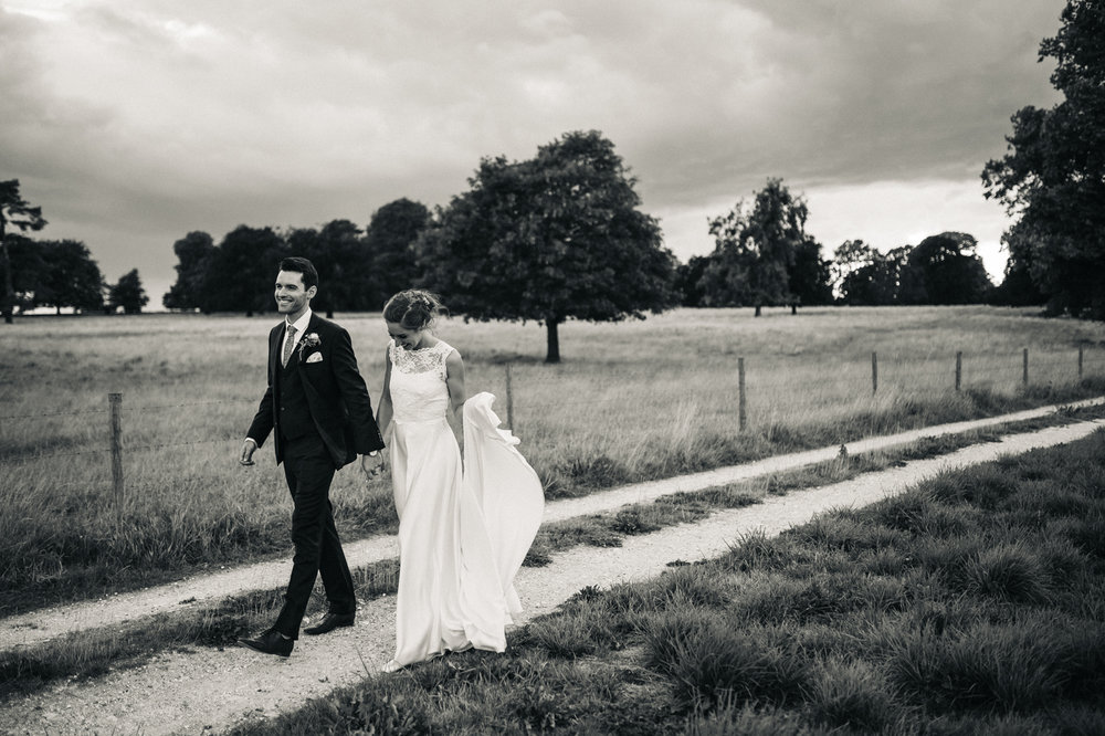 a black and white shot of a bride and groom walking alongside a field. aldby park wedding york north yorkshire teesside photography stop motion wedding films uk