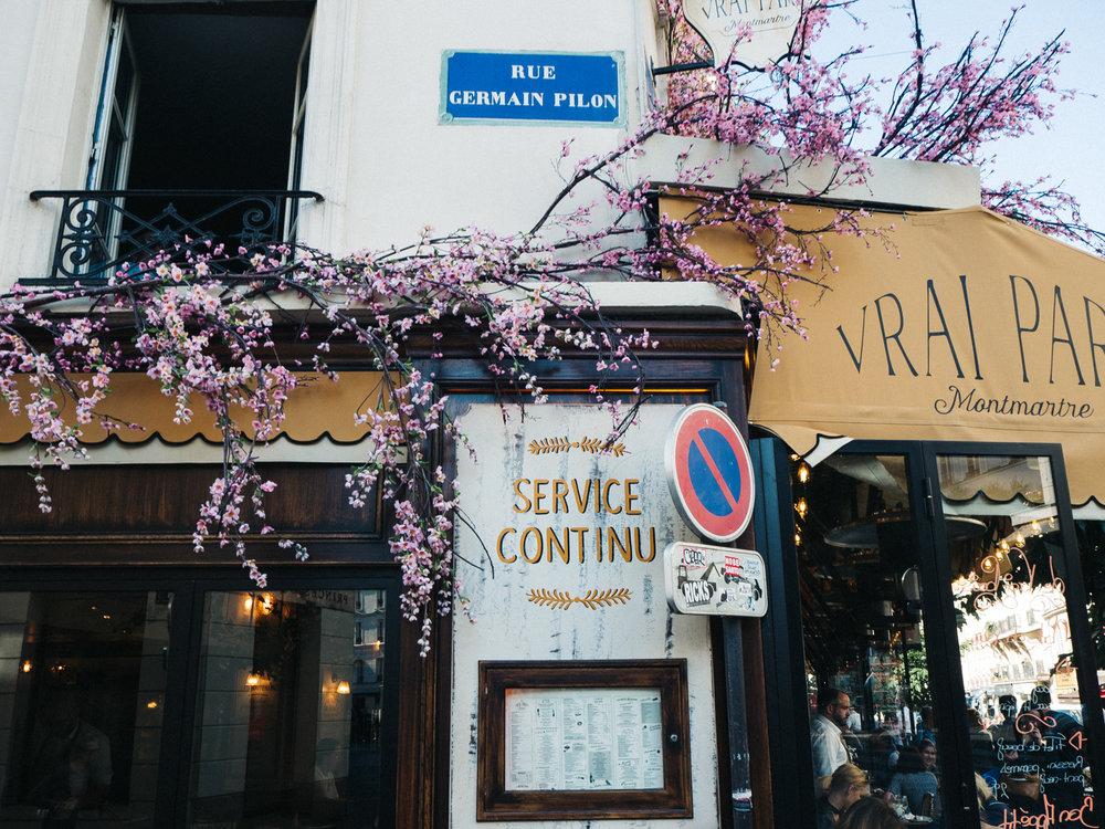 a shot of a blossom-covered shop front in paris. creative travel photography travel blog paris france destination wedding photographer stop motion wedding films uk