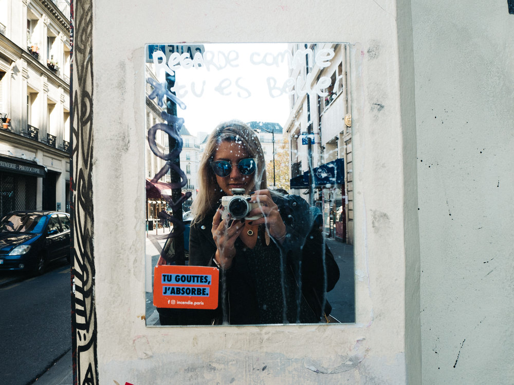 a reflection 'selfie' in a mirror covered in graffiti. creative travel photography travel blog paris france destination wedding photographer stop motion wedding films uk
