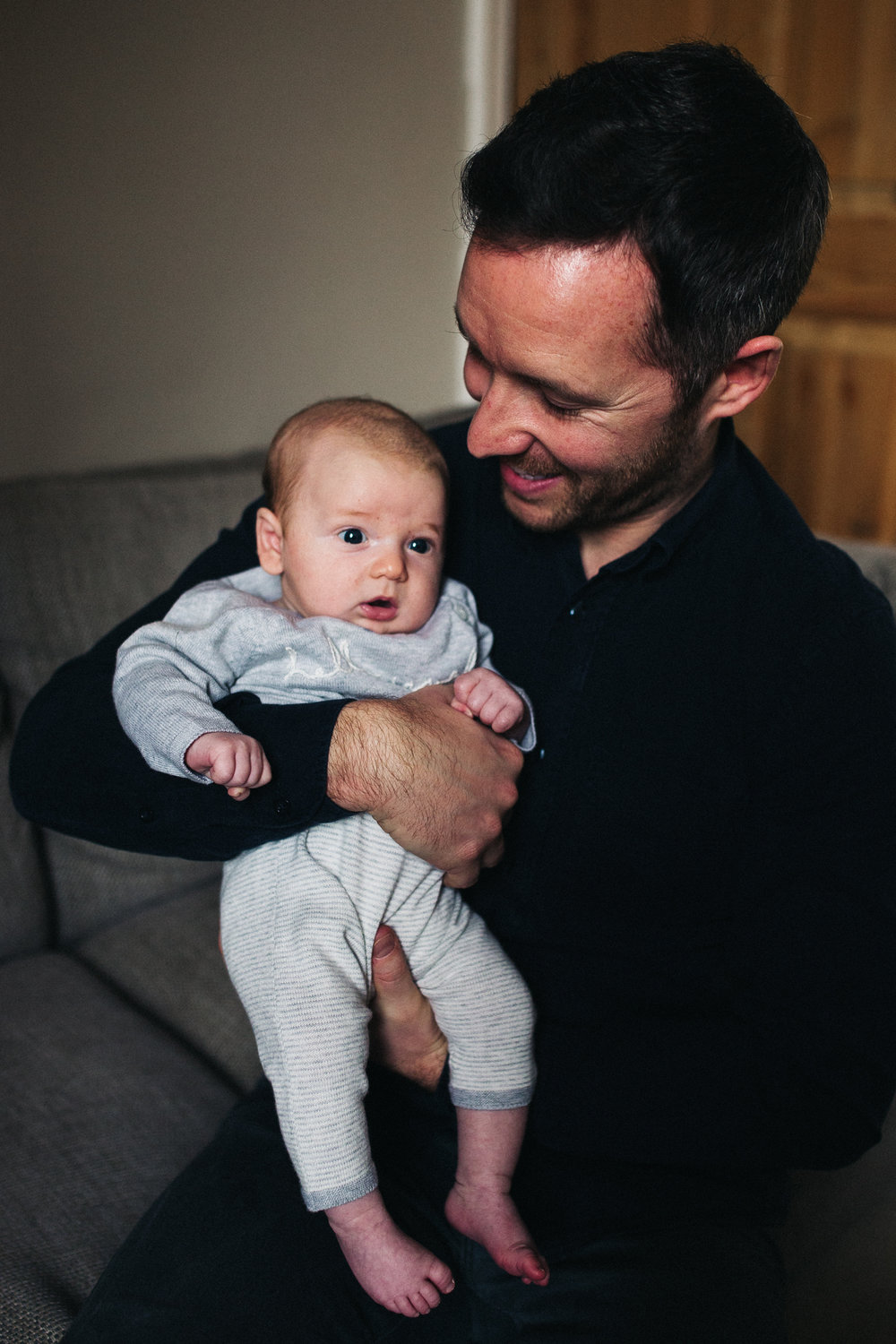a man holds his son and looks at him. creative and relaxed family photography at home teesside middlesbrough stockton north east north yorkshire. stop motion wedding films uk